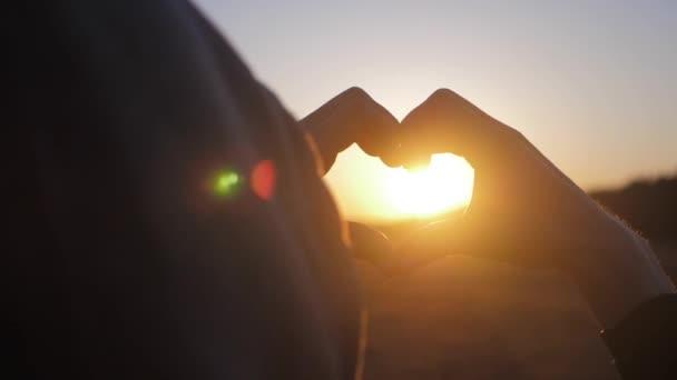 junges schönes Mädchen macht Herz an ihren Händen in Herzform, die die untergehende Sonne bei Sonnenuntergang einrahmt. emotionales Konzept des glücklichen exklusiven Lebensstils Moment, Zeit teilen, entspannen.
