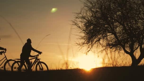 Pár turistů jezdí na kole po silnici. Dvě siluety cyklistů na pozadí západu slunce. Sport a aktivní život koncept čas západu slunce.