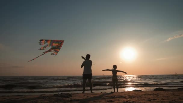 Happy family father and child daughter launch a kite on beach at sunset. Funny family time. Concept of friendly family, travel and freedom.