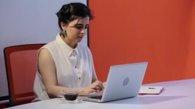 Businesswoman working with tablet computer and documents in office.