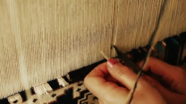 Carpet weaving. Turkish woman weaving a carpet with peace of genuine camel wool with a manual waving machine.