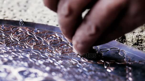 traditionelle Klempnerarbeit. Kupferschmied stellt Prägearbeiten aus Kupfer her. Utensilien entwerfen, die uralte Handwerkskunst. Kupferstich. Souvenirs. Schießen Nahaufnahme Kupferschmied Arbeit.