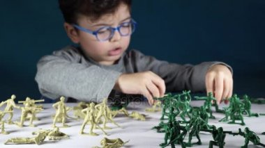 Five year old boy playing with toy soldiers