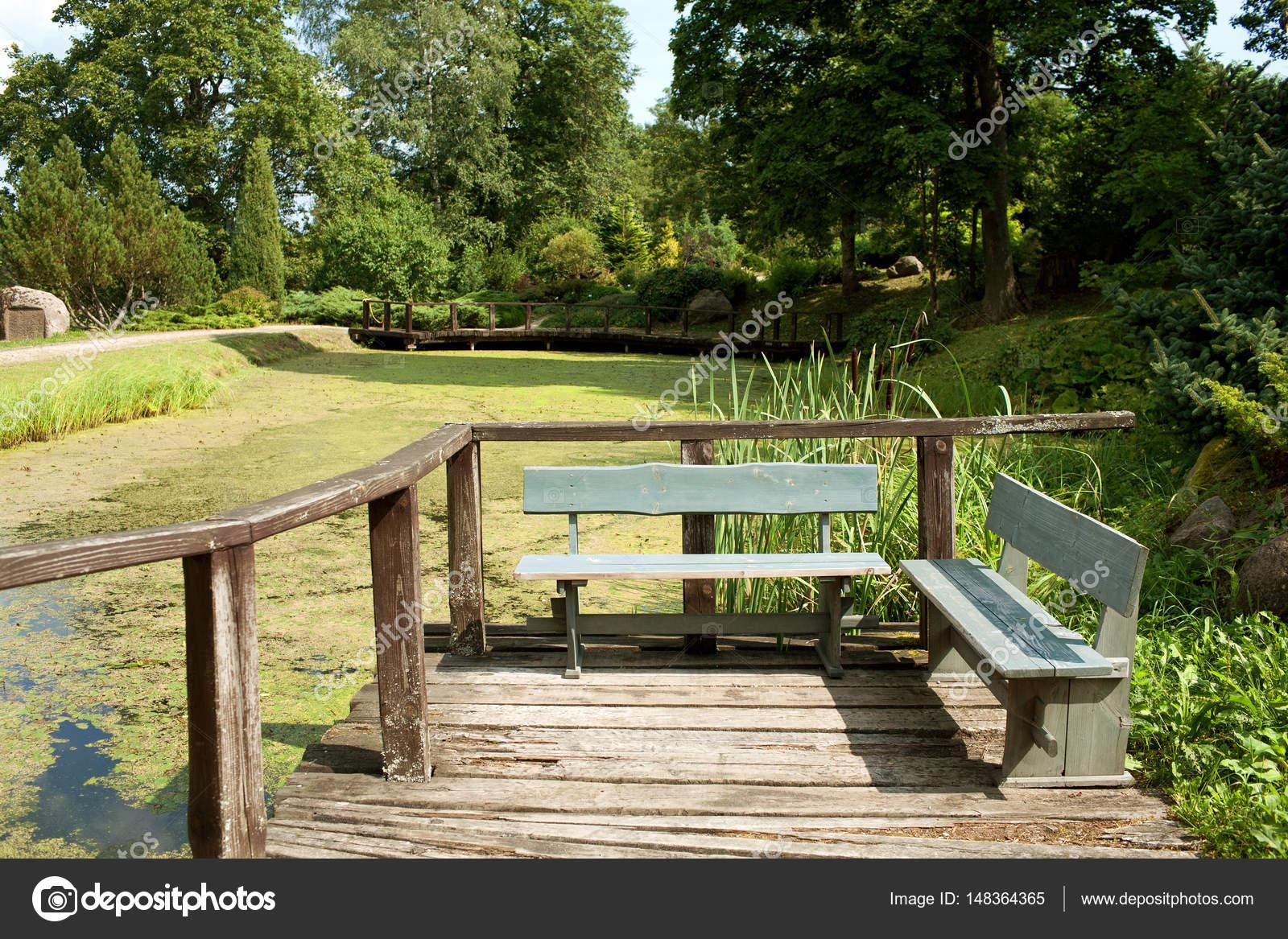Holzbänke an einem alten Teich — Stockfoto © telev #148364365