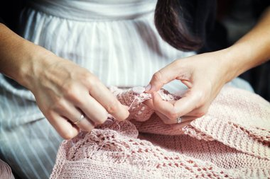 Close-up of a woman in a striped dress sews a button with a thread on a pink sweater, which she herself tied stock vector