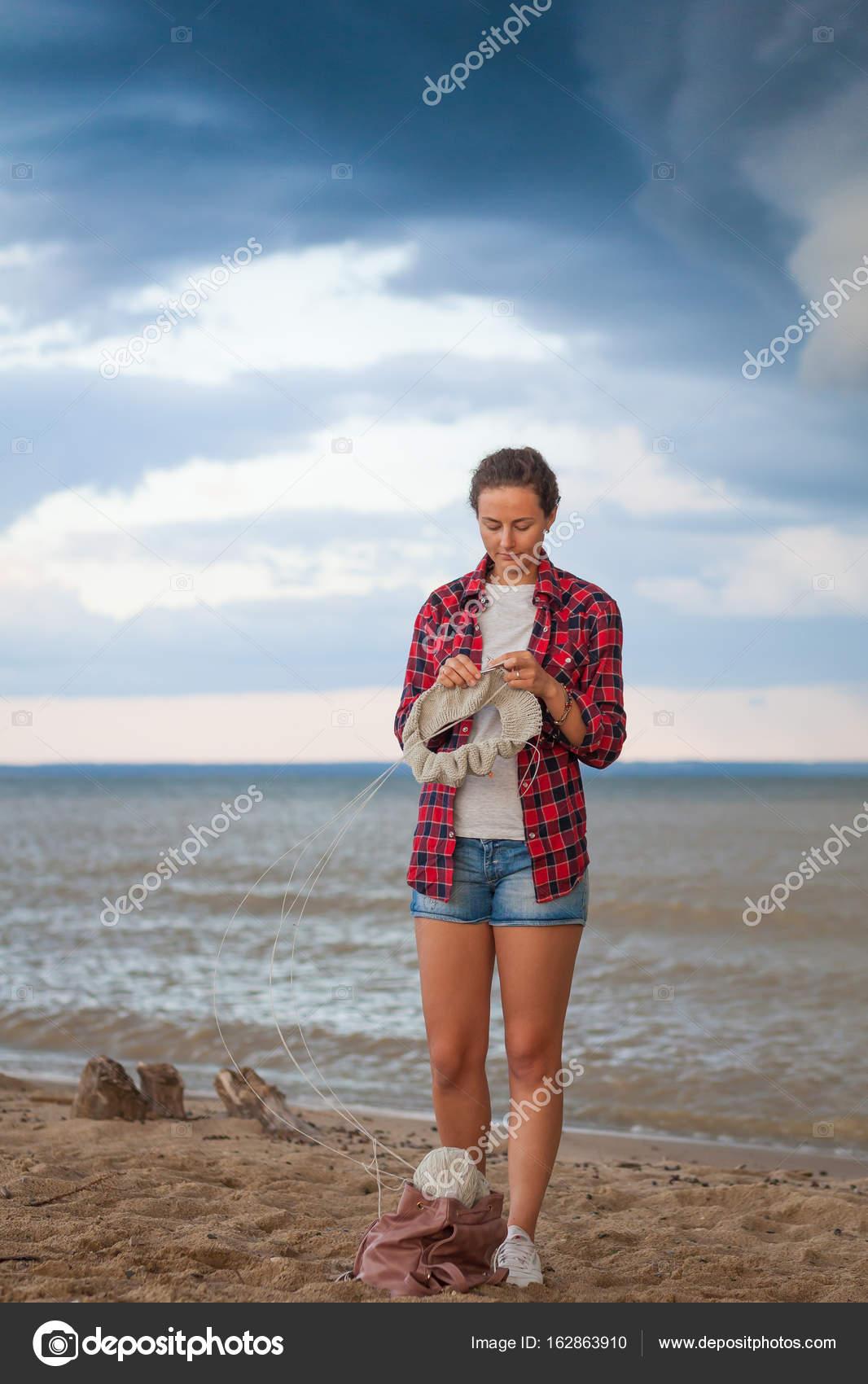c82b3bc3781a ... πλεκτά με βελόνες πλεξίματος ένα γκρι πουλόβερ που γίνονται από φυσικό  νήμα μάλλινο πουλόβερ και στέκεται πάνω στην άμμο κοντά στη θάλασσα — Εικόνα  ...