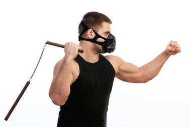 A young athletic man in a sport shirt, a training black mask holds a nunchaks on a white isolated background