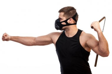 Young athletic man in sports t-shirt, training black mask with nunchaks  on white isolated background