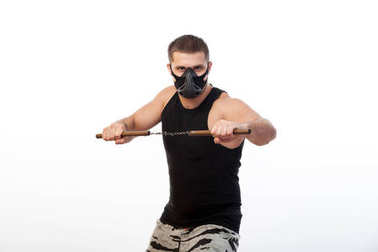 Young sporty blue-eyed man in a sporty black T-shirt, wearing boxing gloves and a black training mask is holding a mettalic nunchak on a white isolated background