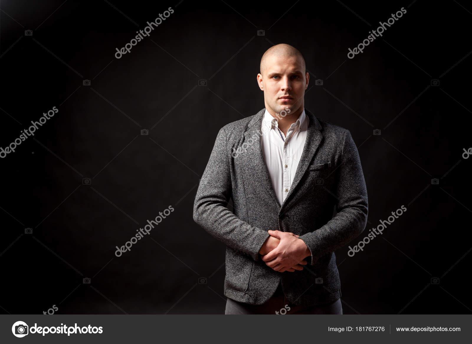 1cba5e73dee14e Un giovane uomo calvo in una camicia bianca, abito grigio con fiducia  esamina la macchina fotografica e tiene le sue mani sulla sua giacca su  sfondo nero ...
