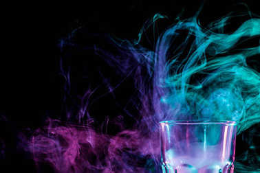 Close up of a new glass with soft multi-colored purple and green smoke from vape on a black isolated background stock vector