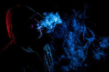 A young man in a black hood smokes a vape and exhales a colored blue smoke on a black isolated background