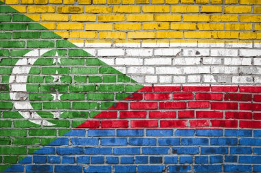 National flag of Comoros  depicting in paint colors on an old brick wall. Flag  banner on brick wall background.