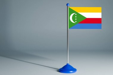 The 3d rendering  realistic national flag of Comoros on steel pole on gray isolated background.  Blank table flag , suitable for design, mocku