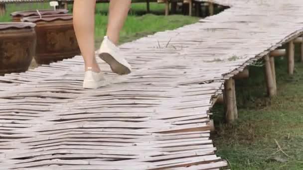 Zárja be a lassított felvétel után balra cipő séta Park alatt napsütéses nyári napon. bambuszbrigáddal.