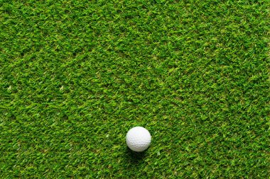 Golf ball on green grass texture of golf course for background.