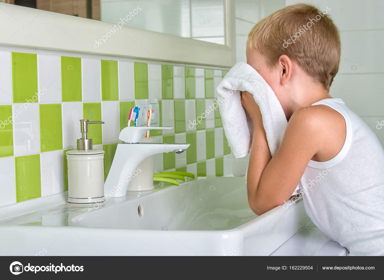 Un Niño Lava La Cara Limpia Su Rostro Con Una Toalla En El Baño