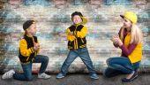 Fényképek Egy fiatal anya, két fiatal hip hop stílusban. Divatos család. Graffiti a falakon