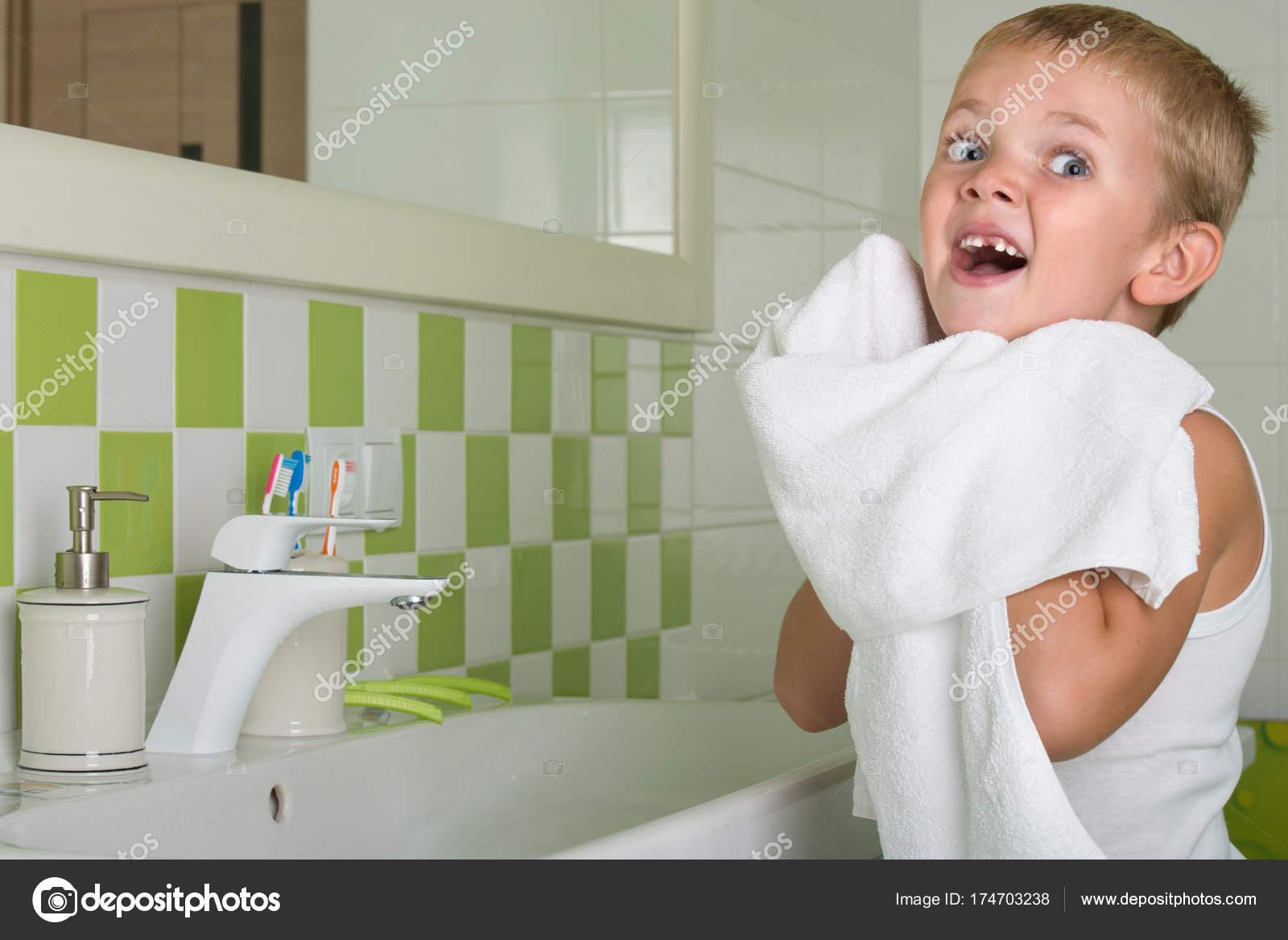 Bagno Con Un Ragazzo : Un ragazzo si lava la faccia pulisce il viso con un asciugamano