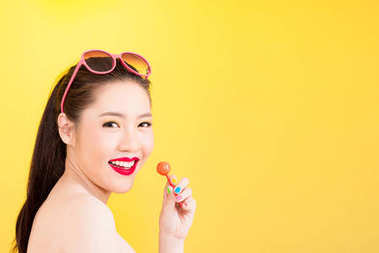 Young Asian woman holding lollipop isolated on yellow background