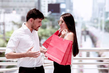 Couple argue after a hard day of huge sale shopping in asian country. Unhappy young handsome white male and beautiful asian girl with shopping bag looking very satisfy as she spent all his money.