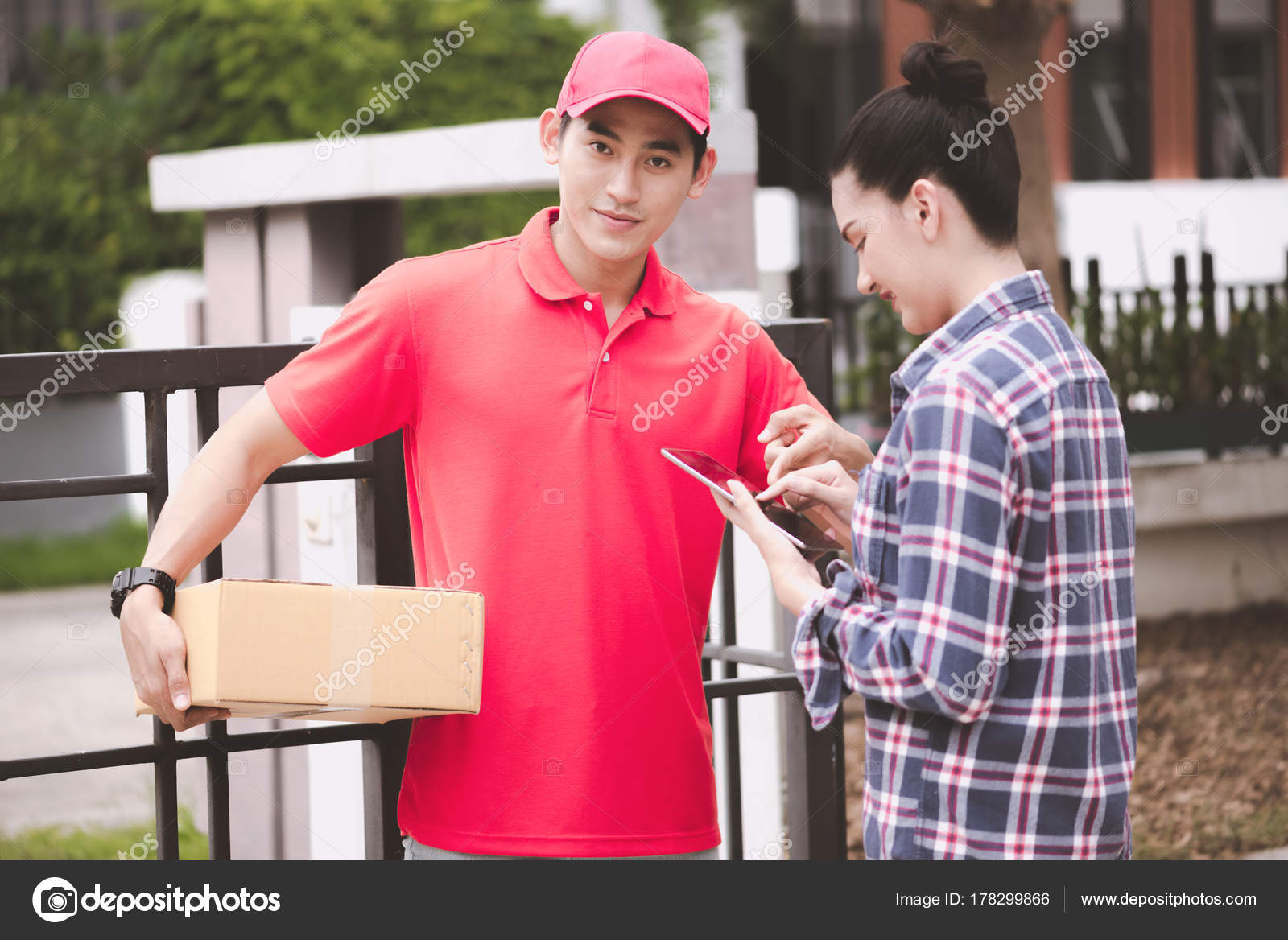 705852308f Happy delivery man giving his package to customer at home. Taken in real  house. Asian chinese fit man in red polo shirt and jeans with red hat in ...