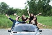 Playboy Party Konzept. junger weißer Mann im Cabrio-Sportwagen mit vier schönen asiatischen Frauen, die auf einer unbeschwerten Party in Freiheit posieren.
