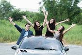Fotografie Playboy Party Konzept. junger weißer Mann im Cabrio-Sportwagen mit vier schönen asiatischen Frauen, die auf einer unbeschwerten Party in Freiheit posieren.