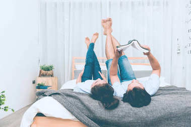 Mixed race lovers concept. Young white male reading a book in his bedroom with his pretty young chinese girlfriend to join. Wearing blue jeans, blue shirt and in their early twenties. Taken indoor.