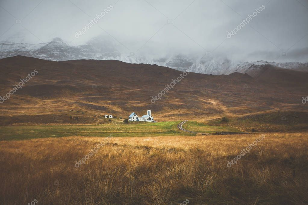 Farm in front of a empty mountain range with fog and snow. Lovel