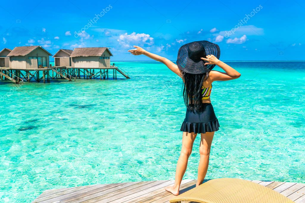 Portrait of happy young woman at beautiful water villa at Maldiv