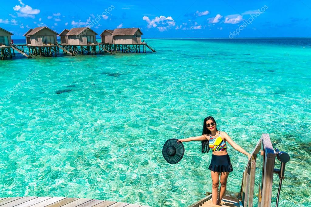 Portrait of happy young woman at beautiful water villa at Maldiv