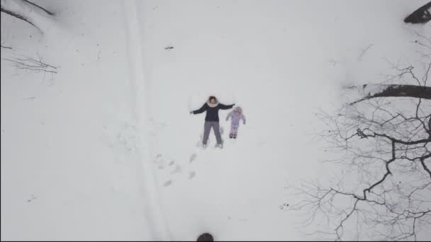 Mom with a child play in a snowy meadow in winter in nature, outdoors, together.