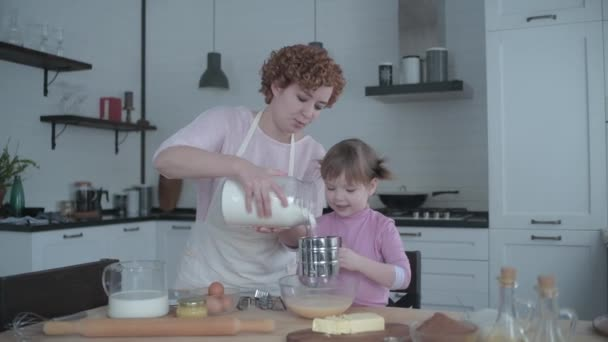 Mom with daughter in the kitchen kneads the dough on a plate. A girl is naughty in the kitchen. Mom plays with the little daughter a cook. The mother teaches her child to cook. Cheerful cooking baking.
