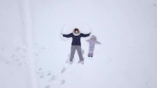 Mom with daughter makes a snow angel in a winter park. A little girl plays in the snow in the winter forest with her mom. A young family lies in the snow in winter in a park. The warmly dressed child walks in the winter.
