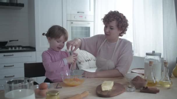 Máma s dcerou v kuchyni peče těsto na talíři. Ta holka je zlobivá v kuchyni. Máma si s dcerou hraje na kuchařku. Matka učí své dítě vařit. Veselé pečení.