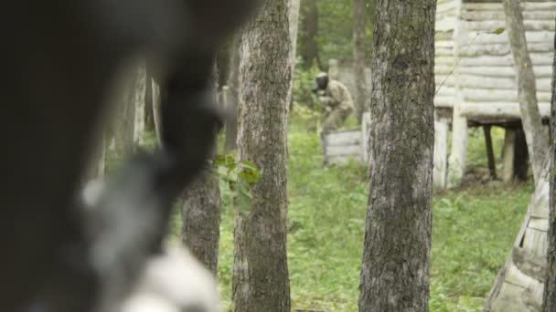 Lidé hrají paintball v lese