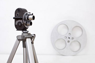 old 8 mm camera and film reel on white