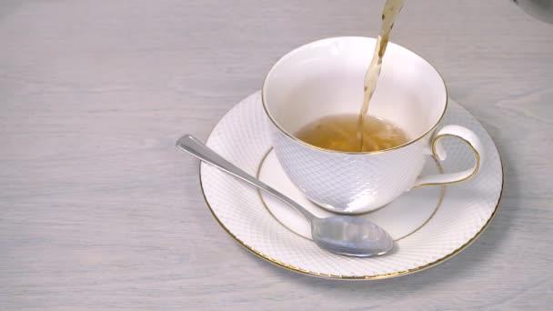 nalití horkého čaje do šálku bílé