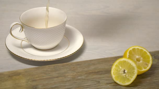 Čaj nalévání do šálku bílého čaje na dřevěný stůl