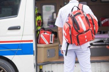 nurse carry nursing bag on his back standing beside ambulance pr