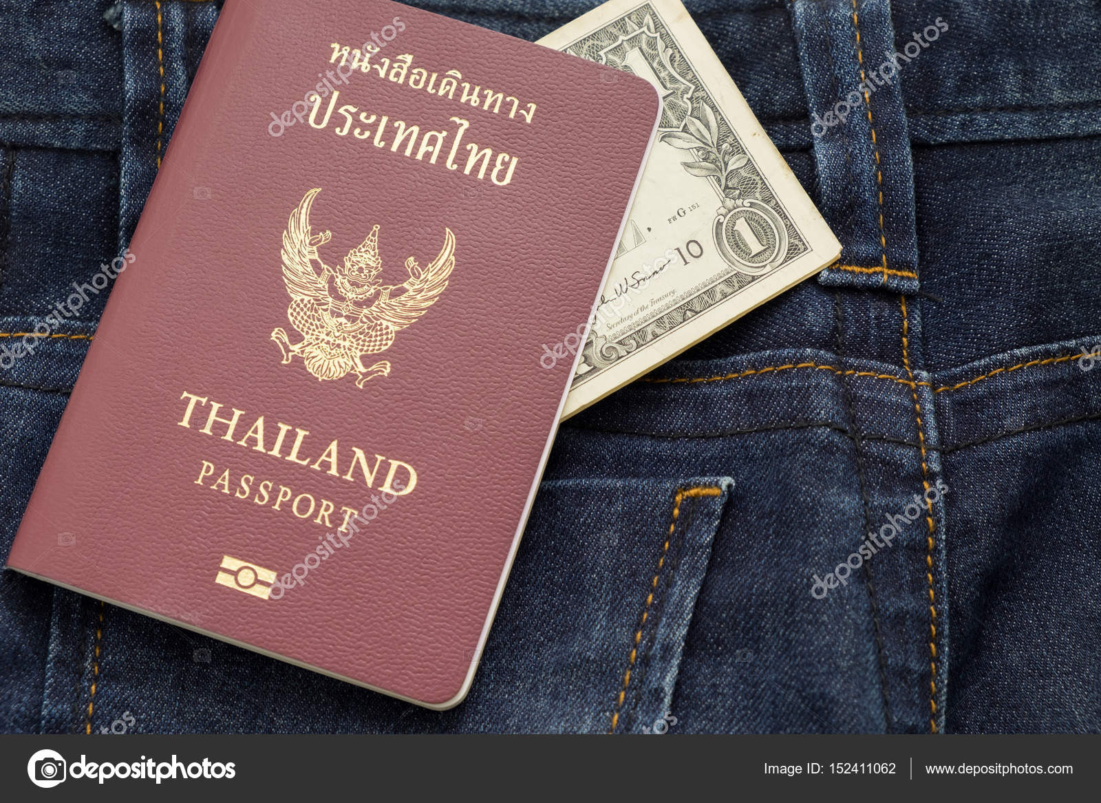 Thailand passport and dollar cash putting on blue jean pants