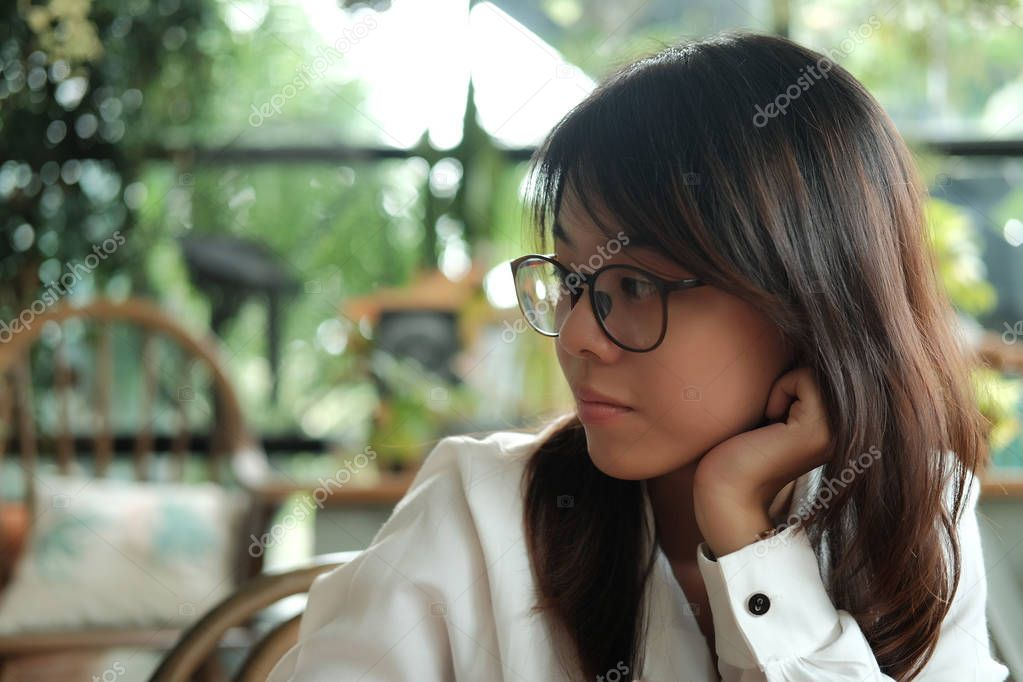 young woman wearing glasses thinking and waiting someone in coff