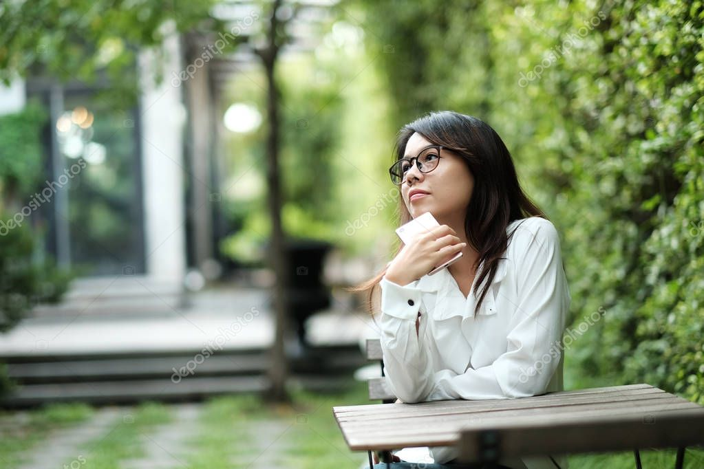 young woman wearing glasses sitting at green public garden. she