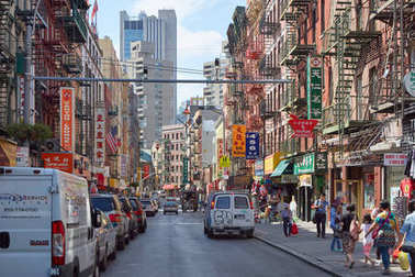 Chinatown street with people and buildings in the morning in New York