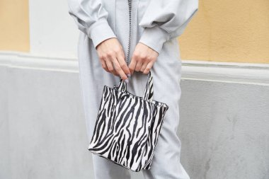 MILAN, ITALY - SEPTEMBER 22, 2019: Woman with gray overalls and zebra pattern bag before Boss fashion show, Milan Fashion Week street style stock vector