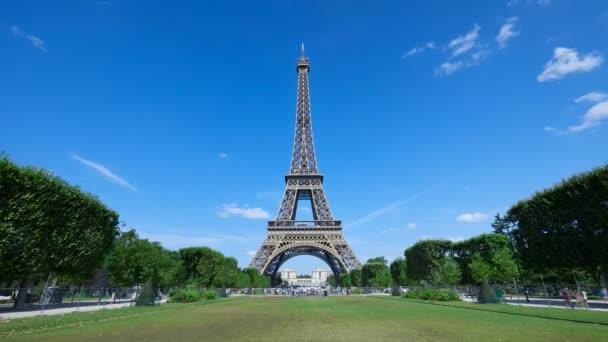 Eiffelova věž časová prodleva, slunečný letní den s modrou oblohou a zeleným polem Marsu v Paříži