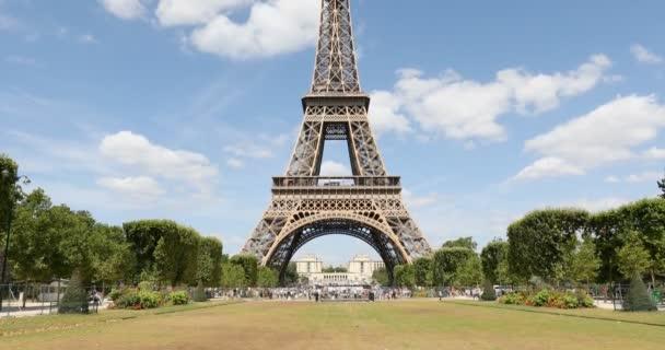 Eiffelova věž v Paříži a zelené louky na Marsu, lidé a turisté, výhled na náklon za slunečného letního dne, modrá obloha