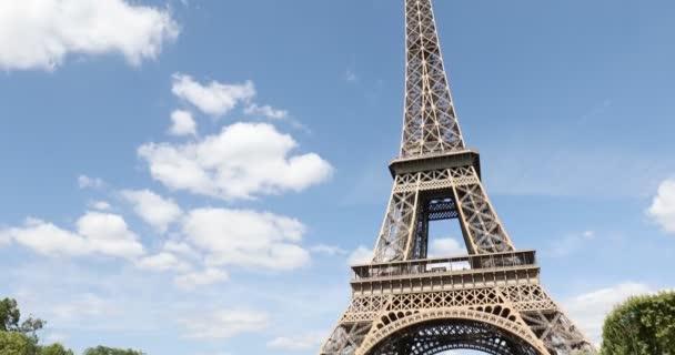 Eiffelova věž v Paříži za slunečného letního dne, výhled z boku, modrá obloha ve Francii