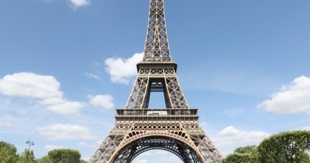 Eiffelova věž v Paříži za slunečného letního dne se zelenými stromy, modrá obloha ve Francii